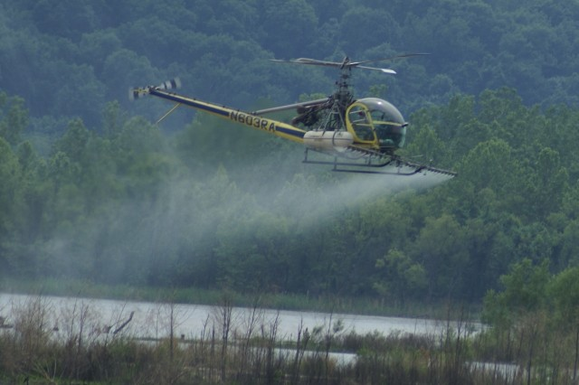 A helicopter sprays an EPA-approved herbicide over an Interior Least Tern island along the McClellan-Kerr Arkansas River Navigation System in Oklahoma. This was the first time a helicopter was used. In the past, the Tulsa District sprayed by boat, which was more time consuming, costly and less effective.