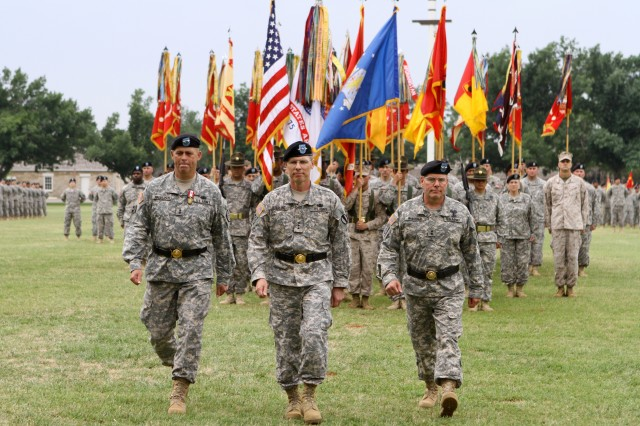 Maj. Gen. David Halverson, former Fires Center of Excellence and Fort Sill commanding general, Lt. Gen. John Sterling Jr., Training and Doctrine Command deputy commanding general and chief of staff, and Maj. Gen. Mark McDonald, new FCoE and Fort Sill commanding general, walk toward the audience after the transfer of the FCoE colors signifying the change of leadership. The change of command ceremony was conducted May 4 at the Old Post Quadrangle here.