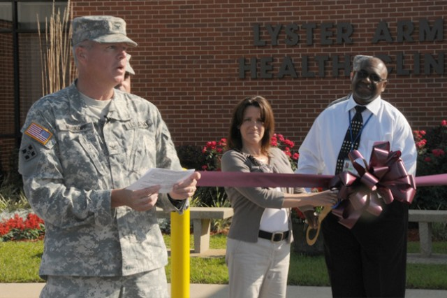 Col. James A. Muskopf, Fort Rucker, Ala., garrison commander, speaks as two Lyster Army Health Clinic patients wait to cut the ribbon at the re-opening ceremony.