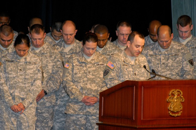 Soldiers bow their heads as Chaplain (Capt.) Stephen Dicks begins a prayer before a mass re-enlistment for the 40th Military Police Internment and Resettlement Battalion May 3 at the Lewis and Clark Center, Fort Leavenworth, Kan.