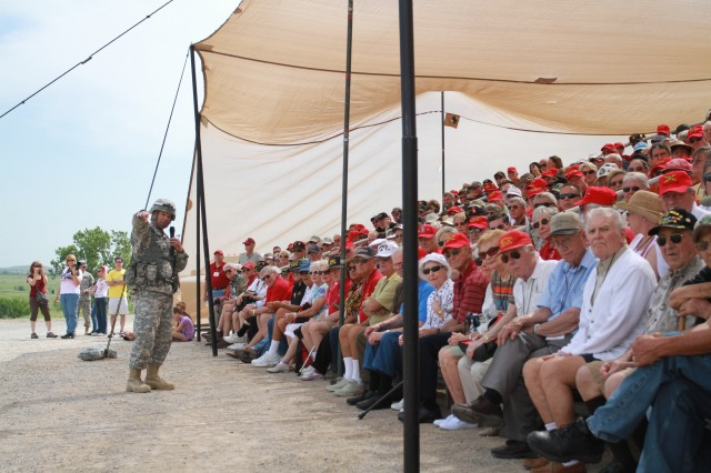 Col. David Lewis directs the attention of Field Artillery Officer Candidate School alumni and their guests during a live fire exercise May 3, at MowWay Observation Point.