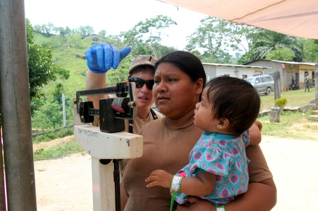 A Soldier assigned to Task Force Tropic weighs a Honduran mother and her child during a Dental Readiness Training Exercise near Naco Cortes, Honduras, May 1, 2012, as part of Beyond the Horizon 2012.