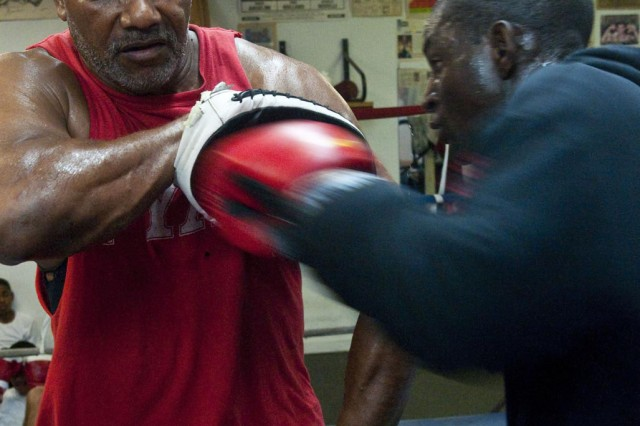 "Nathaniel ""Sweet Red"" Fitch, left, a boxing team coach, uses focus mitts to help sharpen William Simmons' skills, May 1, at Fitch's Boxing Club in Spring Lake."