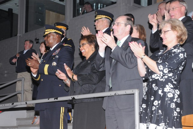 """Army Vice Chief of Staff Gen. Lloyd J. Austin and his wife applaud with friends and guests during the U.S. Army Military District of Washington's """"Twilight Tattoo,"""" held in Conmy Hall at Joint Base Myer-Henderson Hall, Va., May 9, 2012. The show, hosted this week by Austin, is normally performed outdoors but due to some nasty weather in the capital region it was moved inside of the large Conmy Hall."""