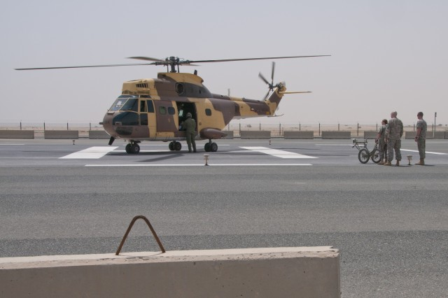 U.S. Soldiers from the 325th Combat Support Hospital (Forward) stand ready beside a Kuwaiti military helicopter outside the troop medical clinic at Camp Arifjan, Kuwait, as part of a medical evacuation exercise, April 26, 2012. The Kuwaiti aircrew begins to unload a simulated casualty injured by a simulated active shooter. Third Army is dedicated to shaping the future by holding joint exercises with partner nations.