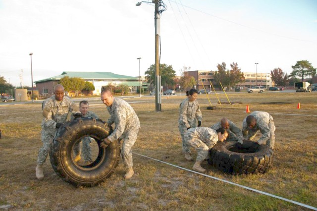 """Soldiers from 2HBCT, 3rd ID, participate in the """"Tire Flip"""" as part of the many varying exercises that has been implemented into the brigade's cross-fit physical fitness program."""