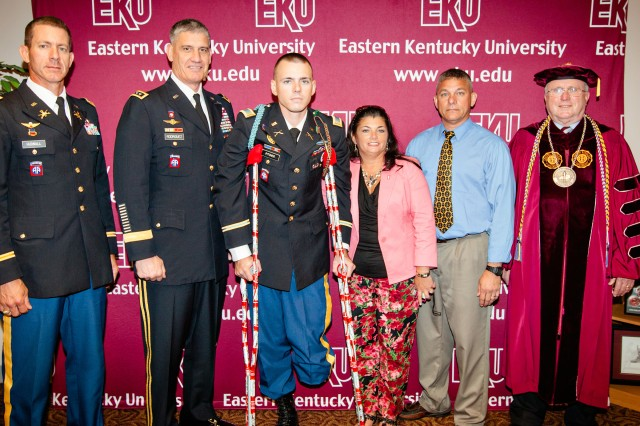 Second Lt. Josh Pitcher of the 82nd Airborne Division made it to the Eastern Kentucky University with the help of Gen. David M. Rodriguez to witness his fiancée, Michelle Smith, graduate. Himself a 2011 EKU graduate, Pitcher was wounded in Afghanistan. Rodriguez arranged for Pitcher to fly with him to EKU. Besides attending his fiancee's graduation, Pitcher also attended the EKU ROTC commissioning. Shown here are (left to right) Lt. Col. Ralph Hudnall Jr., professor of military science at EKU; Rodriguez, commanding general of U.S. Army Forces Command, and a former commander of the 82nd Airborne Division; Pitcher; his mother Vickie Pitcher; his father retired Maj. Randy Pitcher; and Doug Whitlock, the president of Eastern Kentucky University.