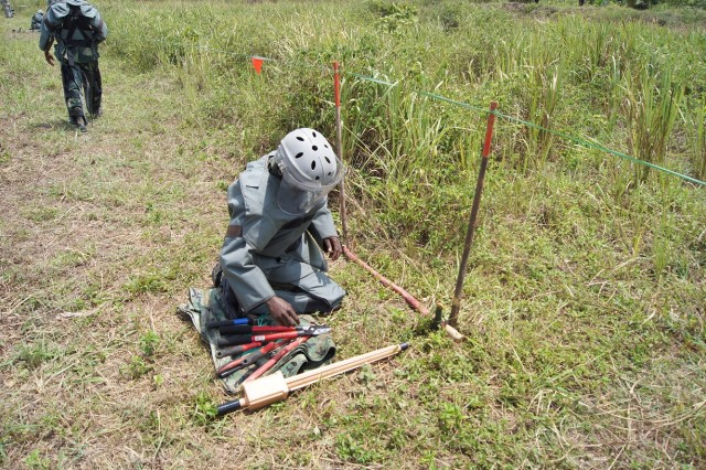 A Congolese soldier with the Forces Armées de la République Démocratique du Congo (FARDC) starts a one-man drill, a methodical and deliberate procedure to conduct minefield clearance . The stick that is in front of him is a one-meter stick that is slowly inched forward as his lane is cleared. This engagement, which is part of the Humanitarian Mine Action program, took place April 6- 27 at Camp Base in Kisangani, the capitol of the Orientale Province in the Democratic Republic of the Congo.