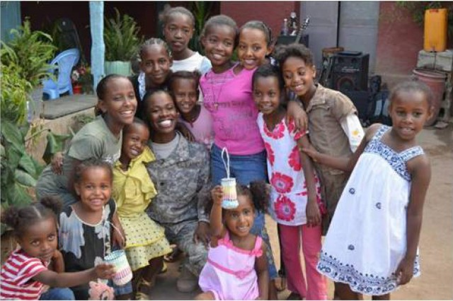 Girls from the St. Augustine Orphanage pose for a picture here with U.S. Army Spc. Rose Lee, Task Force Raptor, 3rd Squadron, 124th Cavalry Regiment, Texas Army National Guard, April 4. Lee is part of the Women's Initiative Program headed by the U.S. Army 490th Civil Affairs Battalion in support of Combined Joint Task Force - Horn of Africa.