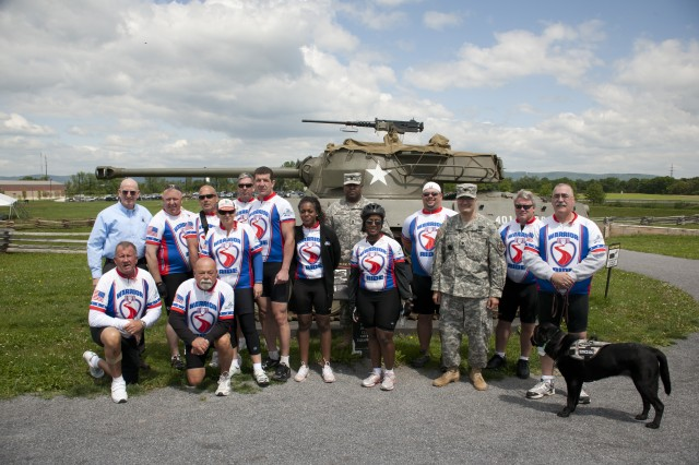 Maj. Gen. Gregg Martin, USAWC Commandant, Lt. Col. William McDonough, garrison commander and CSM Robert Blakey, pose for a group photos with members of the Warrior Ride before they depart the United States Army Heritage and Education Center May 10. Photo by Scott Finger.