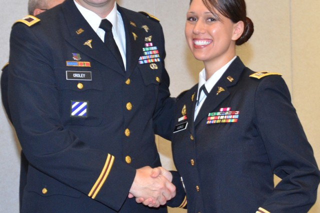 Captain Justina Assmus receives her Master of Physician Assistant Studies diploma from Col. Mark Croley, the CRDAMC acting deputy chief of clinical services, during a ceremony at the hospital May 11 (Photo by Brandy Gill, CRDAMC Public Affairs).