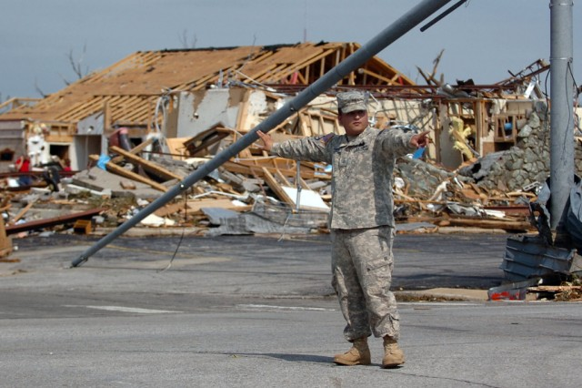 Pfc. Jesus Ramos, 1139th Military Police Co., Missouri Army National Guard, directs traffic at a storm-damaged intersection near St. John's Mercy Hospital last May in Joplin, Mo., following the tornado.