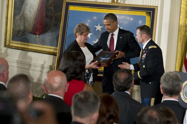 Rose Mary Brown, widow of Spc. 4 Leslie H. Sabo Jr., 101st Airborne Division, accepts Sabo's Congressional Medal of Honor at the White House in Washington, May 16, 2012. Sabo was killed in action on May 10, 1970.