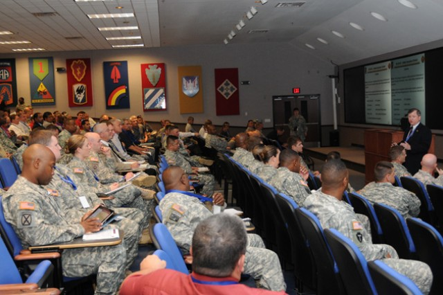 Members of the Air Traffic Services community gather in a conference room to listen to Stewart Wyland, chief of airfield operations for IMCOM, talk about IMCOM airfield updates and the way ahead May 8.