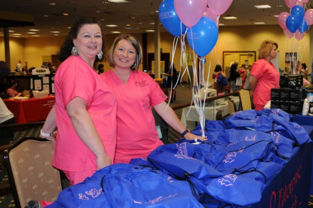 Shannon Wehunt and Ashley Grubbs hand out bags of gifts and information about the Enterprise Women's Center.
