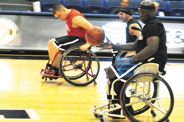 Retired Cpl. Perry Price III, of Wilmington, Del., races down the basketball court alongside retired Spc. Juan Soto, a San Antonio, Texas, native, at a wheelchair basketball game against the Marines during the 2012 Warrior Games in Colorado Springs, Colo.
