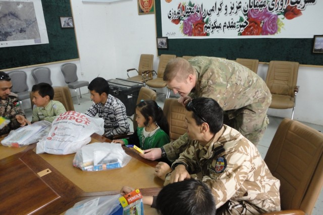 Afghan children examine donated school supplies with Capt. Chad Daniels (upper top right), trainer-mentor for the 1-335th Infantry Battalion, 205th Infantry Brigade, who started a toy drive to reach out to the children in his area of operation. Coalition partners contributed to the joint effort. (Photo courtesy First Army Division East)