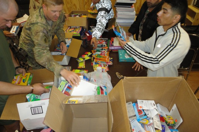 Capt. Chad Daniels (upper left), trainer-mentor for the 1-335th Infantry Battalion, 205th Infantry Brigade, loads boxes of school supplies with volunteers from the Afghan National Army. Daniels and volunteers from First Army Division East collected more than 400 toys and numerous school supplies for the children of Pol-e-Charki, Afghanistan. (Photo courtesy First Army Division East)