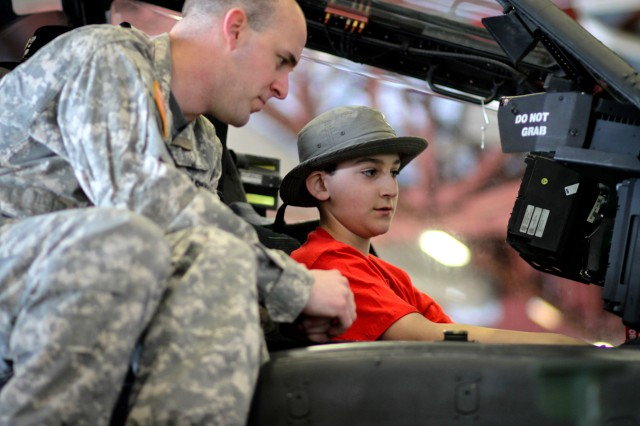 Capt. Joseph Sinkiewicz, a pilot with B Company, 1st Battalion, 10th Aviation Regiment, shows off the cockpit of his Apache helicopter to Jimmy Watson, a Boy Scout from Troop 99 visiting Fort Drum on Saturday from the Albany area. Watson was part of a group of Boy Scouts visiting for the weekend to get a taste of Army life and celebrate the values shared by the Boy Scouts and America's military.
