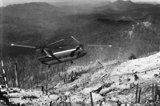 A Chinook hovers over one of the four hilltops that comprised Fire Support Base Ripcord in Vietnam's treacherous A Shau Valley. Helicopter lifeline was the only means of importing/exporting personnel and supplies.