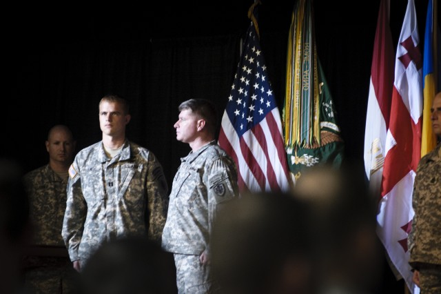 Capt. Chad Lewis (center) and Maj. Gen. Patrick M. Higgins (right) stand at attention as Lewis is awarded the Soldier's Medal for heroic actions taken in July 2010 while assigned as a Special Forces Qualification Course student. Higgins witnessed a catastrophic plane crash in Chapel Hill, N.C. and saved the life of the plane's co-pilot, applying tourniquets and staying with him until medical personnel could arrive.