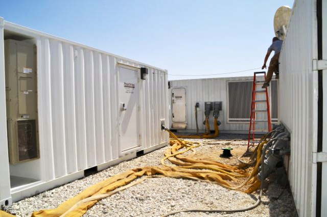 Power generated by two generators in the top center unit is fed to the control unit (right) where the Intelligent Micro Grid computer system distributes reliable power matched to demand loads and peak demand times at a lower cost per kilowatt hour than point generation of electrical power. The 1-megawatt microgrid provides power to more than 60 structures such as the office container (left) at the camp with greater efficiency than the 20 plus generators it replaces.