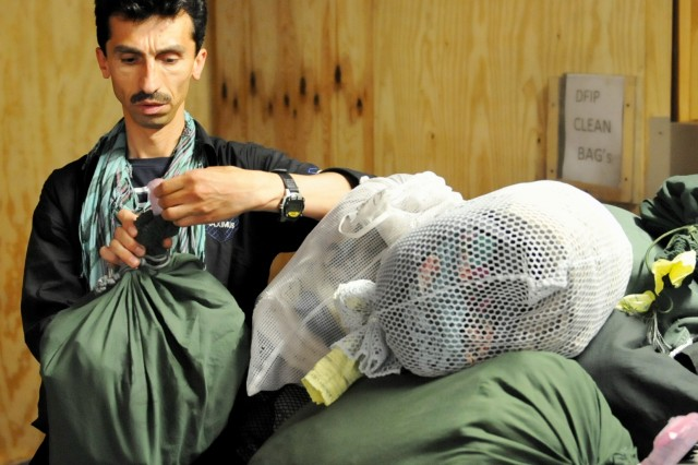 A  Fluor contractor from Afghanistan processes laundry at Bagram Airfield, Afghanistan, May 15. Approximately 9,000 Afghan workers are employed by LOGCAP contractor Fluor. LOGCAP is under operational control of the 401st Army Field Support Brigade, Army Sustainment Command.