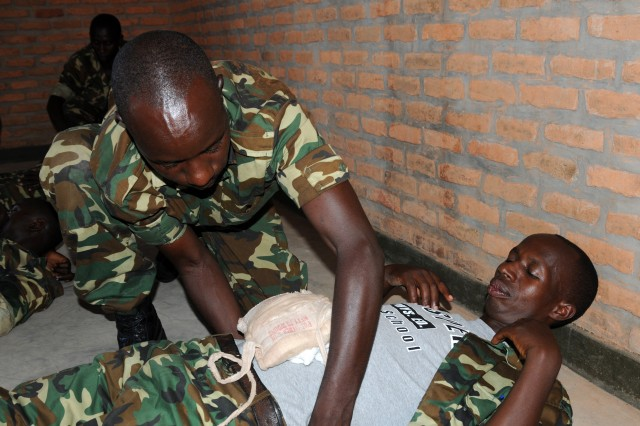 A Burundi National Defense soldier demonstrates how to apply a field dressing during a combat lifesaver course in Mudubugu, Burundi, recently, with U.S. Army Soldiers from Task Force Raptor, 3rd Squadron, 124th Cavalry Regiment, Texas Army National Guard. The guardsmen conducted various military-to-military exchanges in support of Combined Joint Task Force - Horn of Africa to build partnerships with nations in East Africa.