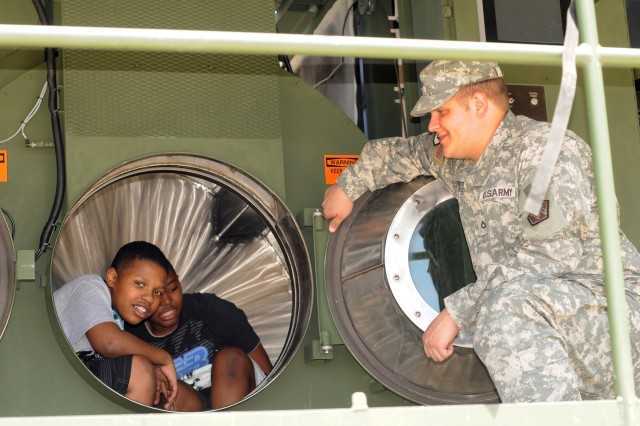 "Pfc. Andrew S. Pfeifer ensures the safety of visitors ""riding"" in the drum of a Laundry Advanced System, or LADS, during the 2012 Joint Service Open House at Joint Base Andrews, Md., May 18, 2012."