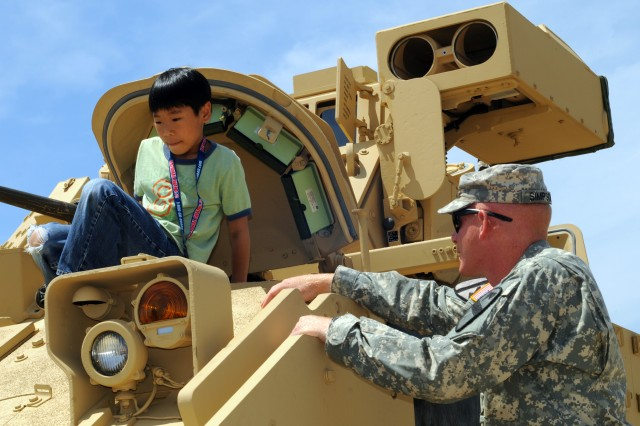 Sgt. Randall Simpson ensures the safety of a visitor exiting an M3A3 Bradley during the 2012 Joint Service Open House at Joint Base Andrews, Md., May 18, 2012.