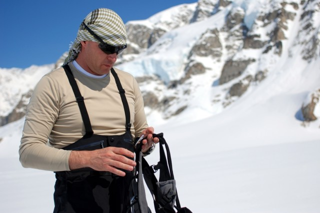 Maj. Gary McDonald, commandant of the U.S. Army Alaska Northern Warfare Training Center, inspects his harness and climbing equipment May 17, 2012, in preparation for his team climb up Mount McKinley, Alaska. Additional protective covering for the exposed skin, like the cloth covering shown here, is vital as reflected solar radiation from the ice and snow can more than double a person's UV exposure on the glacier.