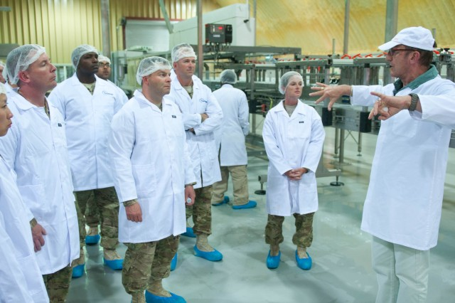 Larry Downes, the technical officer for the NATO Maintenance and Supply Agency water bottling facility at Kandahar Air Field, Afghanistan, briefs Soldiers from the 3d Sustainment Command (Expeditionary) during their tour on May 15. (U.S. Army photo by Staff Sgt. Michael Behlin)
