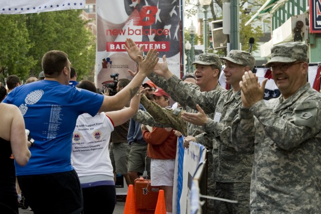 Soldiers high-five runners as they pass by Fenway Park during the Red Sox Run-Walk to Home Base, May 20, 2012. About a dozen active duty Soldiers and civilians from Natick Soldier Systems Center in Natick Mass., joined the nearly 2,000 runners and walkers who participated in the Red Sox Run-Walk to Home Base.  The Run-Walk to Home Base is a unique 9-kilometer fundraising run and three-mile walk which helps raise money for the Red Sox Foundation and Massachusetts General Hospital Home Base Program.