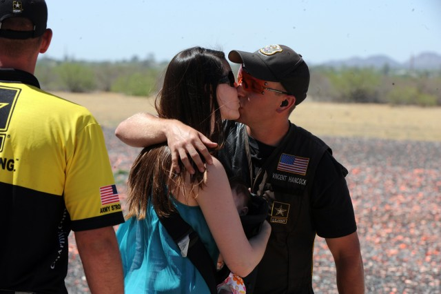 U.S. Army Marksmanship Unit shotgun shooter Sgt. Vincent Hancock receives a victory kiss from wife Rebekah, with 3-month-old daughter Brenlyn squeezed in between, following Hancock's victory Sunday in the men's skeet competition at the 2012 U.S. Olympic Shotgun Team Trials at the Tucson Trap & Skeet Club in Tucson, Ariz. With the victory, Hancock, a gold medalist at the 2008 Beijing Games, secured a berth in the 2012 Olympic Games in London.