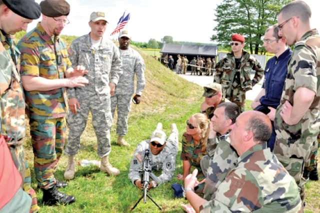Spc. Daniel Donaldson (standing, third from left) and Sgt. Mohammed Echiheb (behind machine gun) describe the operation of an M249 squad automatic weapon at one of the stations at the Monte Kali shooting competition in Wackernheim.