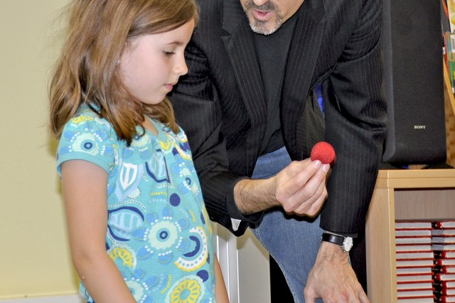 Magician Brian Temple performs a sleight-of-hand trick with the assistance of first-grader Mya Cacciotti during a presentation at Aukamm Elementary School May 11.