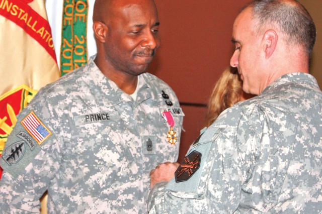 Col. David Carstens, U.S. Army Garrison Wiesbaden commander, pins Command Sgt. Maj. Hector Prince with the Legion of Merit.