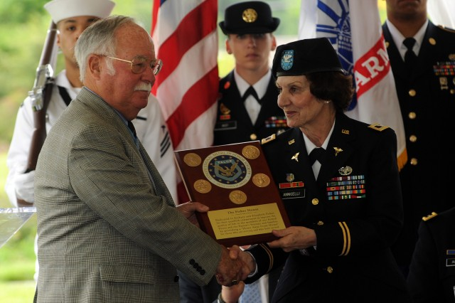 Medal of Honor Recipient Col. H.C. Barnum Jr., who is retired, presents a plaque from the Medal of Honor Society to Col. Susan Annicelli, commander, Fort Belvoir Community Hospital.  The plaque will be placed inside the new Fisher House that opened, May 22, 2012, at Fort Belvoir.