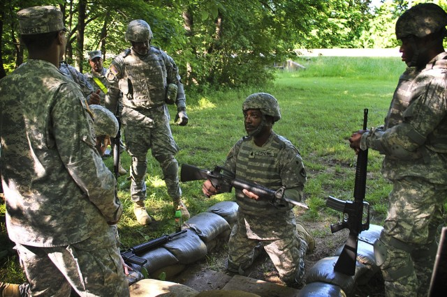 Army Reserve Soldier, Lt. Col. Furman Oxendine (center), presents his fully reassembled M16 rifle during a Warrior Tasks and Battle Drills evaluation at Ramsey Test Track on Rock Island Arsenal, Ill., May 17. Oxendine and his fellow reservists are set to deploy in support of LOGCAP operations in Southwest Asia and were evaluated on individual and collective combat-oriented tasks by Army Sustainment Command personnel. (Photo by Susan Matos, ASC Public Affairs)