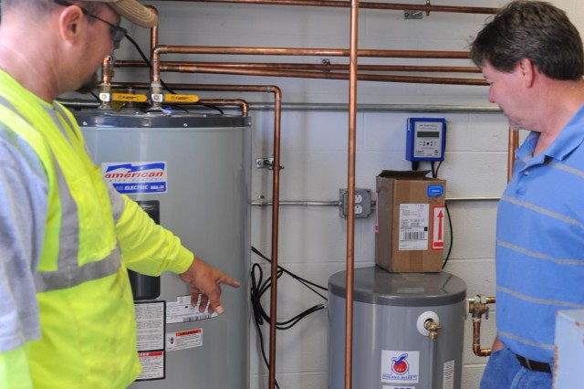Sean Gardner, left, a partner owner for Compass Solar, shows Brian Freeman, an Anniston Army Depot mechanical engineer, how the installation's solar water heater system works.