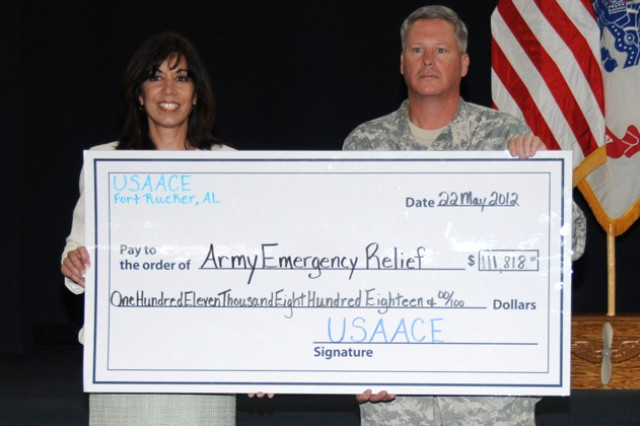 Col. James A. Muskopf, Fort Rucker garrison commander and Army Emergency Relief chairman, presents a check for $111,818 that was raised for the AER campaign raised to Mimi Brooks, Army Emergency Relief officer, during the 2012 AER campaign closing ceremony at the U.S Army Aviation Museum May 22.