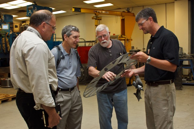 Chris Williams, chief of Anniston Army Depot's turbine drive train division (far right), and mechanic Leonard T. Farrar discuss the depot's turbine engine capabilities with Alan F. Estevez, assistant secretary of defense for logistics and material readiness, and Dwight Dwyer, Army Materiel Command G4 May 23 in the depot's Turbine Engine Repair Facility.