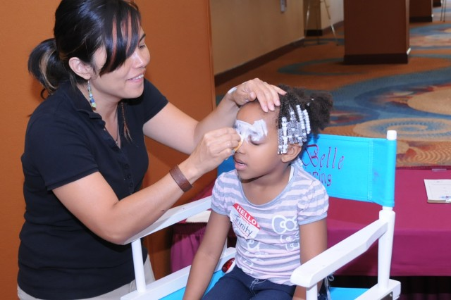 Trinity Coles, daughter of Master Sgt. Cornelia Coles, gets her face painted during a Yellow Ribbon children's activity in Orlando, Fla. The artist, Mila Dykes, was contracted to provide various ddesigns to the children of Soldiers and family members in YRRP sessions.