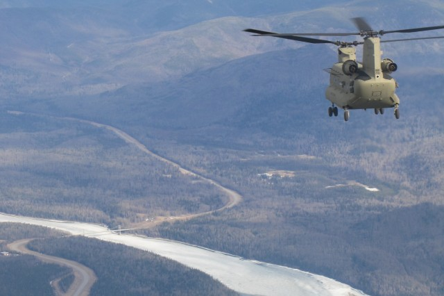 A new CH-47F Chinook helicopter flies high above the Al Can highway during a ferry trip from the southern U.S. to the interior of Alaska. A river can be seen far below winding its way through the Northern Rocky Mountains.