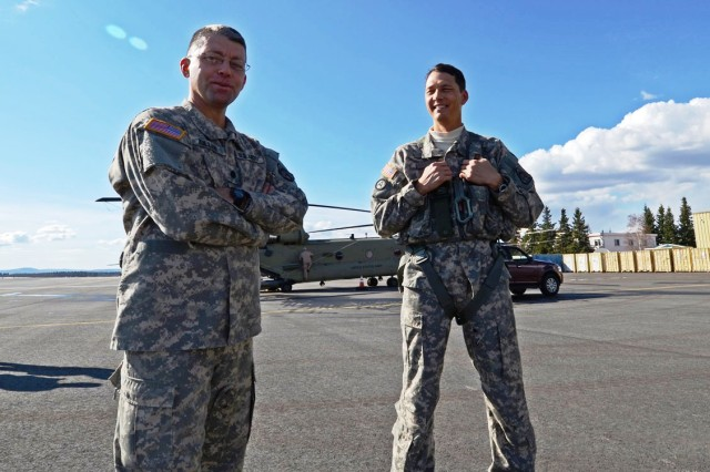 Lt. Col. Brad Killen, left, product manager for the CH-47F, and Col. Bob Marion, Cargo Helicopters project manager, stand on the Ladd Army Airfield parking ramp near eight new CH-47F model Chinooks. The two officers lead the effort to ferry a total of 12 new aircraft to the 1st Battalion, 52nd Aviation Regiment at Fort Wainwright.