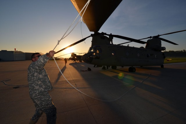 Chief Warrant Officer 5 Matthew Carmichael, a Chinook pilot from the 10th Combat Aviation Brigade, Fort Drum, N.Y., pulls a blade rope into position for removal at an airport in St. Louis. He joined a small task force consisting of active duty Army, National Guard and civilian crew members to ferry 12 CH-47F model Chinooks to the 1st Battalion, 52nd Aviation Regiment in Fairbanks, Alaska, in April.