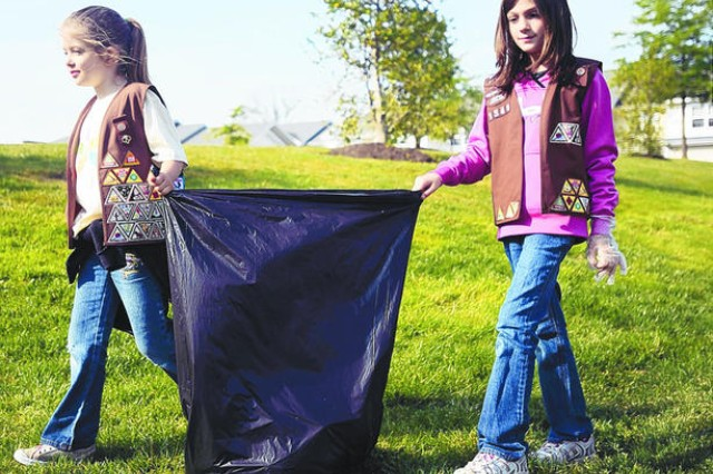 Eight-year old Girl Scouts Ashley Brooks and Kyla Hay scan a grassy hill in Meuse Forest for trash during the Enlisted Spouses Club's fourth annual Clean Up Fort Meade on April 21. Girl Scout troops have been meeting on post since the 1940s. (File photo)