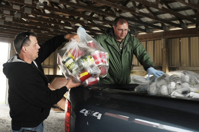 George Stever grabs a bag of recyclables from John Rebelo at the Self- Serve Recycle Drop-Off Center on Thursday during the postwide cleanup event. Both men, who visit the center at least once a week to deposit recyclables, work for the Directorate of Logistics at Wheeler-Sack Army Airfield.