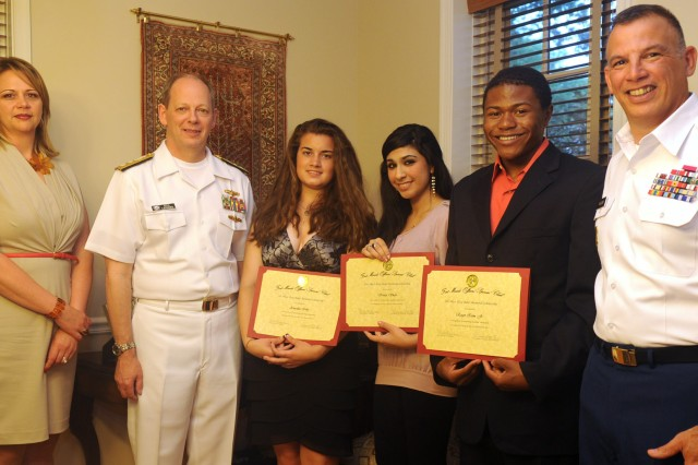 Navy Rear Adm. William Leigher, director of the Navy staff's Warfare Integration for Information Dominance at the Pentagon, and Garrison Commander Col. Edward C. Rothstein congratulate Annalisa Irby and Kinza Shah, graduating seniors at Meade High School, and Roger Isom Jr., a graduating senior at Broadneck High School in Annapolis, all winners of the Officers' Spouses' Club's Etta Baker Scholarship.