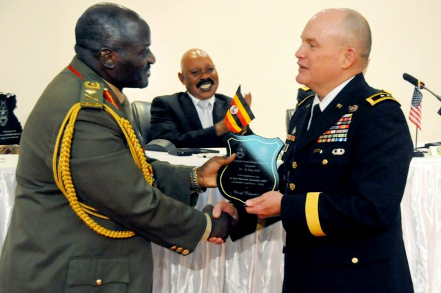 Ugandan Land Force Chief Lt. Gen. Edward Katumba Wamala, and Maj. Gen. David R. Hogg, commander, U.S. Army Africa present gift to each other at the closing ceremony for the African Land Forces Summit 2012, May 18.
